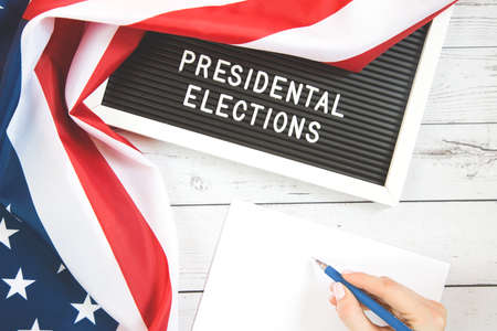 november 3 2020, 59th presidential election in USA. Flat lay composition: United states flag on white wood background. Vote by Mail Ballot envelopes for election. Stock Photo