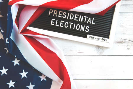 november 3 2020, 59th presidential election in USA. Flat lay composition: United states flag on white wood background.