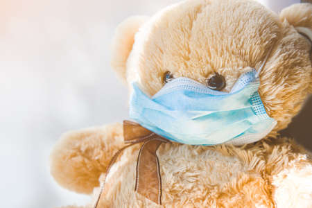 A teddy bear toy in a medical mask during the coronavirus epidemic. Quarantine in kindergartens and schools. Closing educational institutions, stay home.
