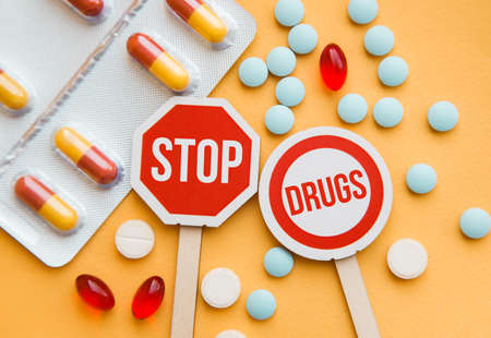 Sign Stop drugs. Colorful pile of medicines and painkillers on yellow background