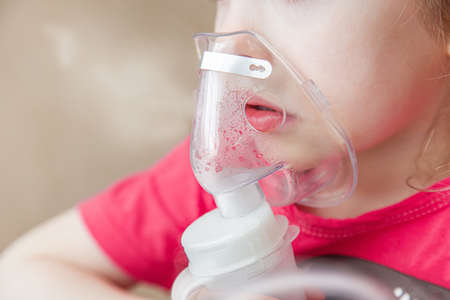 little child girl of three - four years is ill, is treated with a nebulizer, cough. bronchitis treatment Фото со стока