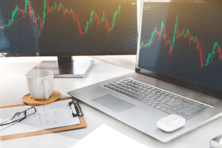 laptop and monitor with exchange charts. Trading discussion and analysis of stock market trading chart, stock chart concept