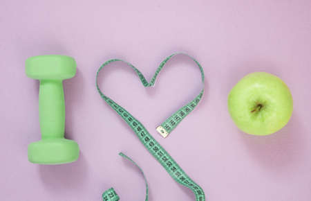 i love healthy eating. Dumbbells, apple, measuring tape on purple background. sport, healthy lifestyle concept Фото со стока