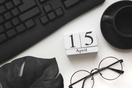 Desktop top view. 15 April tax day. Calendar, glasses and a sheet of paper on a white table flat lay