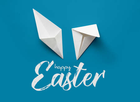 Happy Easter. rabbit ears made of paper on a blue background Фото со стока