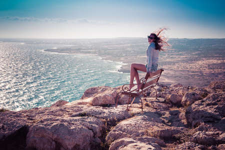 Girl sitting on bench on the top of Cape Greco in Cypruss
