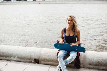 beautiful blonde woman posing with a skateboard
