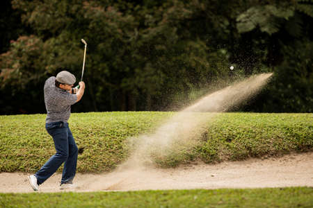 Professional golfer. hits the ball from the sand trap