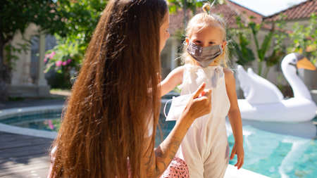 little girl puts on a mask for mom