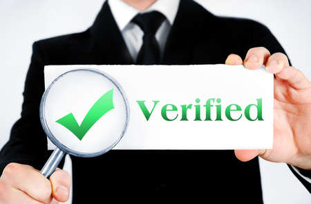 Business man magnifying verified word photo