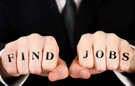 Businessman showing find jobs word on fist photo