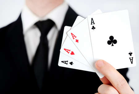 Business man showing 4 aces photo