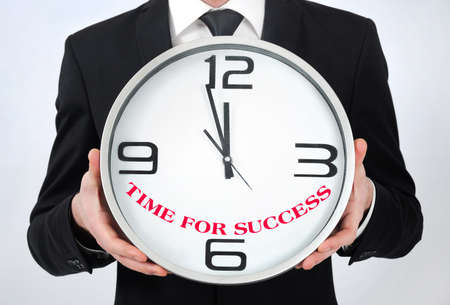 Businessman holding clock with time for success photo