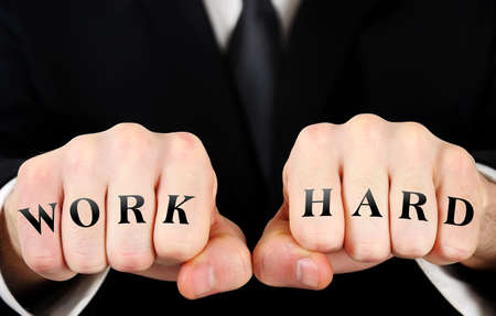 Business man showing work hard word on fist photo