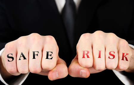 Businessman showing safe and risk word on fist photo