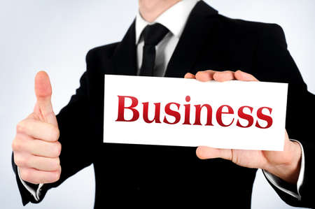 Businessman showing business word on card photo