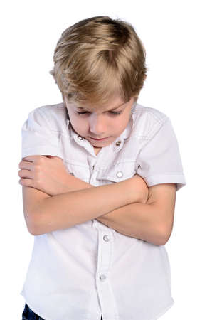 upset young boy with crossed arms on white photo