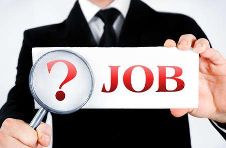 Business man magnifying job word photo