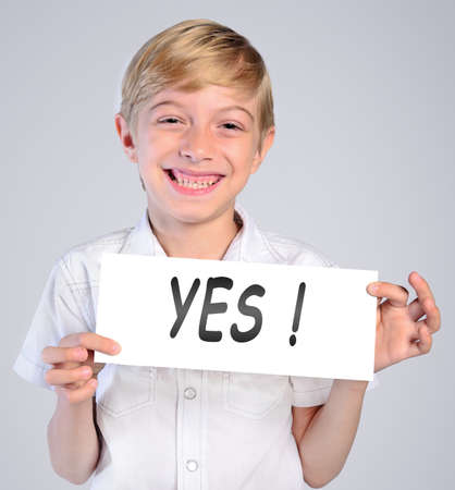 denote: little boy holding paper with yes word