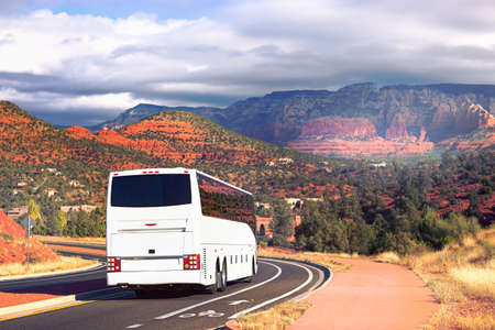 cornering: White tourists bus cornering on street road in Sedona, USA. Bus with tourists on the background of the city of Sedona. Bus with tourists on a background of red rocks in the valley Sedona city Stock Photo