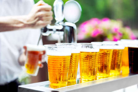 Man drawing beer from tap in an plastic cup. Draught beer. The bartender pours a beer in a plastic cup. On the bar table are plastic cups with a beer