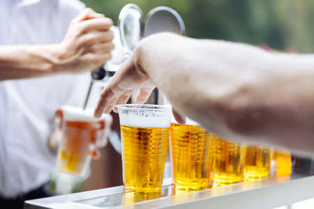 draught: Man drawing beer from tap in an plastic cup and hand oh another man takes beer plastic cup Draught beer. The bartender pours a beer in a plastic cup. On the bar table are plastic cups with a beer Stock Photo