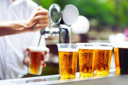 Gráfico del hombre cerveza de grifo en un vaso de plástico. Cerveza de barril. El camarero vierte una cerveza en un vaso de plástico. En la tabla de la barra son vasos de plástico con una cerveza