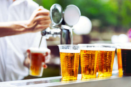 beer foam: Man drawing beer from tap in an plastic cup. Draught beer. The bartender pours a beer in a plastic cup. On the bar table are plastic cups with a beer