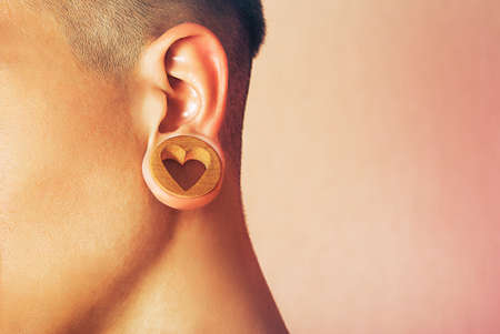 ear ring: A piece of jewelry that fits into a stretched earlobe hole. Man with ear tunnel. Male ear with a ring