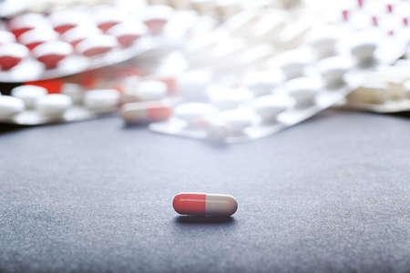 pharmaceutics: Single orange-white capsule. Single tablet on background with many medicine orange and white capsules.  Background of orange tablets. Medications. Pink pills. Abstract pharmaceutics background.