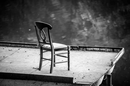 Black and white photography of lonely chair on a floating bridge at lake at evening. Lonely chair on pontoon near water.