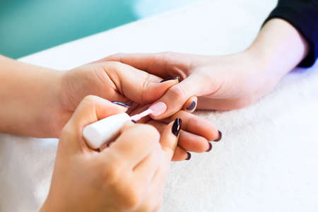 varnish for the nails: Close-up of beautician applying colorful varnish. Applying nail polish on nails with a brush for applying nail polish on fingers. Manicure nail applicator in a beauty salon. In a beauty salon varnish