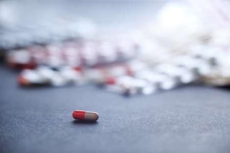 pharmaceutics: Single orange-white capsule. Single tablet on background with many medicine orange and white capsules. Background of orange tablets. Medications. Pills. Abstract pharmaceutics background.