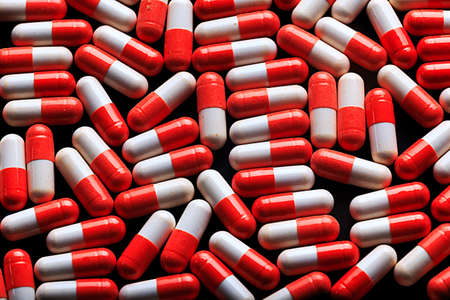 pharmaceutics: Many medicine red and white capsules. Background of red tablets. Medications. Red pills. Abstract pharmaceutics background from the red capsules pils.
