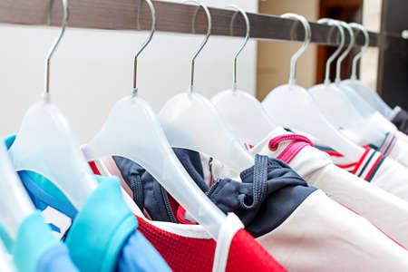 sport clothes: Sport clothes on hangers. Sport clothes on clothes rail in clothing store on hangers. Mans sport clothes hanging in wardrobe. Clothes hanging on the rack in the store. Rod with hangers. Stock Photo