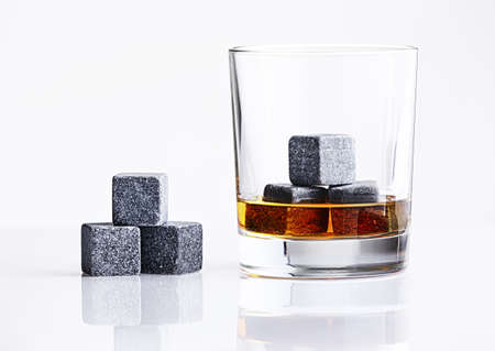 whiskey glass: Close up view of whisky stones in the glass with whisky isolated on white background. Gray whiskey stones in the glass. Whiskey glass filled with cooling granite stones. Bourbon with ice Whisky Stones Stock Photo