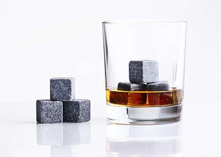 whisky: Gros plan sur les pierres de whisky dans le verre avec du whisky isolé sur fond blanc. pierres de whisky gris dans le verre. verre de whisky rempli de refroidissement des pierres de granit. Bourbon avec de la glace Whisky Pierres Banque d'images