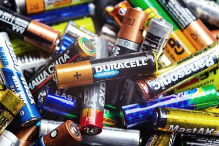 KYIV, UKRAINE - March 03, 2016: Many used Colorful AA and AAA sized batteries in a pile at black background. Concept background of heap of AAA, AA and super heavy duty batteries.