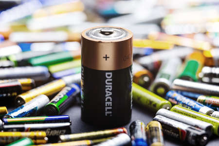 old mercury: KYIV, UKRAINE - March 03, 2016: Heavy duty D type battery on many used colorful AA and AAA sized batteries in a pile at black background. Concept background of heap of AAA, AA and D size battery.