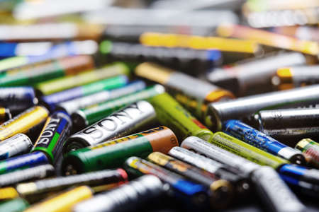 old mercury: KYIV, UKRAINE - March 03, 2016: Many used Colorful AA and AAA sized batteries in a pile at black background. Concept background of heap of AAA, AA and super heavy duty batteries.