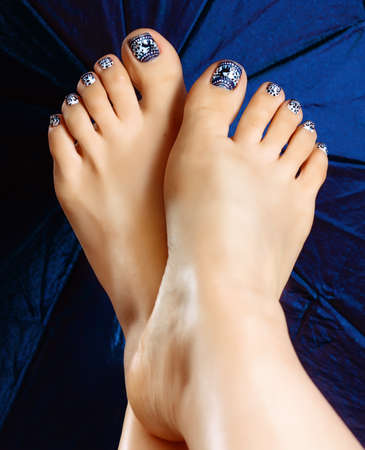 beautiful feet: Female legs pedicure close up view. Nail painting. Delicate winter pedicure. Drawing on nails. Beautiful well-groomed feet with pedicure and varnish on nails and artistic painting.