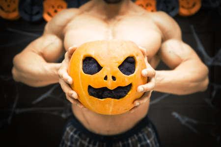 gym halloween theme gym halloween gourd bodybuilder with pumpkin in his hands, a strong man squeezes a pumpkin, sportsman's trunk, strong hands squeeze Halloween pumpkin 스톡 콘텐츠