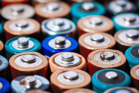 Close up top view on rows of selection of AA batteries energy abstract background of colorful batteries. Alkaline battery aa size. Several batteries are next to each other. Many aa batteries. Stock Photo