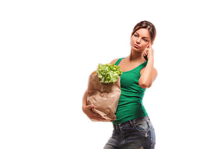 concept of healthy food nutrition. The girl makes purchases thinks about the correctness of the choice of healthy food. Girl with a bag of fruit and vegetables. Stock Photo
