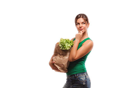 correctness: concept of healthy food nutrition. The girl makes purchases thinks about the correctness of the choice of healthy food. Girl with a bag of fruit and vegetables. Stock Photo