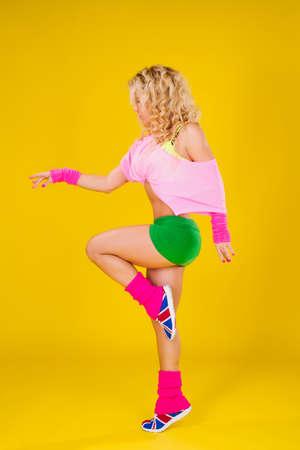 Girl athlete posing on yellow background Zdjęcie Seryjne