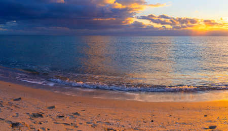 Sandy coast of the Black Sea in the rays of the setting sun (Seascape)