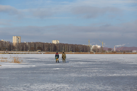 two fishermen return after fishing on the ice of the lake