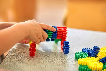 A boy collect a soft puzzle at the table. Preschool children and educational toys