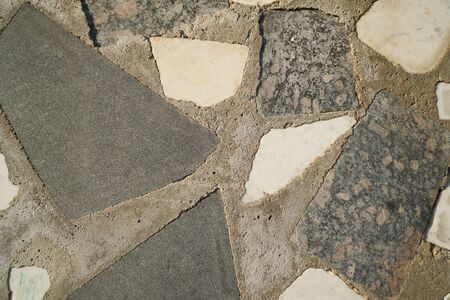 Mosaic wall granite pieces of building in sunny day, pieces of marble and granite bonded with gray cement.